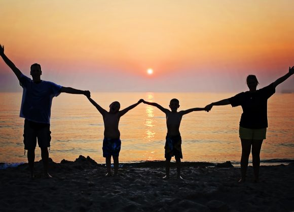 family holding hands on a beach at sunset