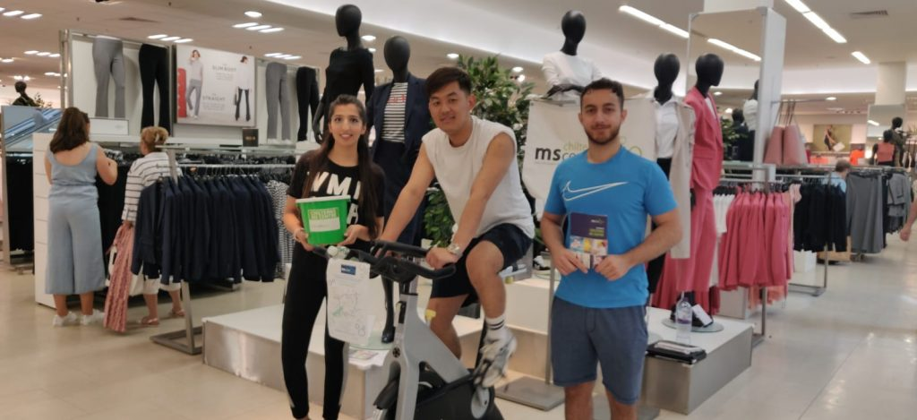 3 members of M&S bank staff doing a static bike ride