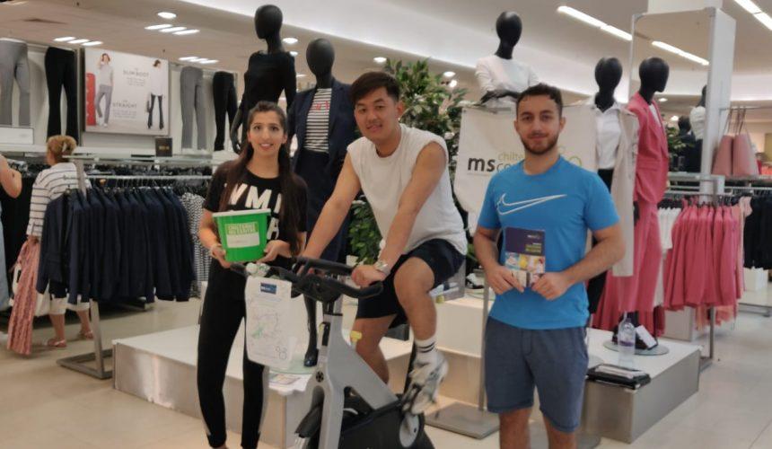3 members of M&S bank staff doing a static bike ride