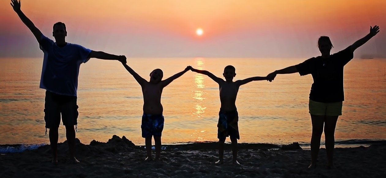family holding hands on beach with sunset in background