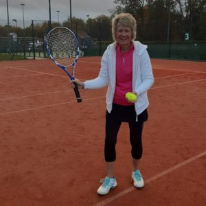 Judith poised with her tennis racket on a court