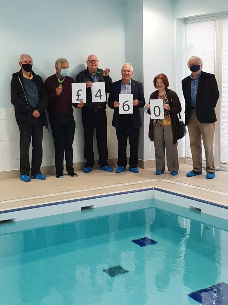 Great Missenden Rotary Club Members standing by the pool holding a £460 sign