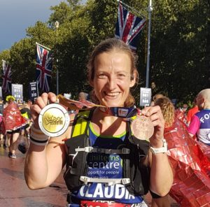 Claudia holding up two medals post London Marathon with a huge smile